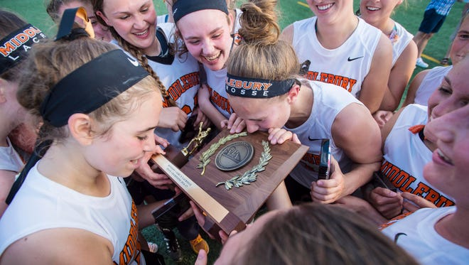 Middlebury players kiss the championship trophy after defeating Mt. Anthony during the Division I girls lacrosse high school state championship  on Monday, June 12, 2017.