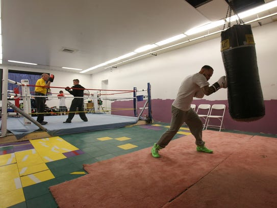 Joey Tiberi works a punching bag (right) as his father