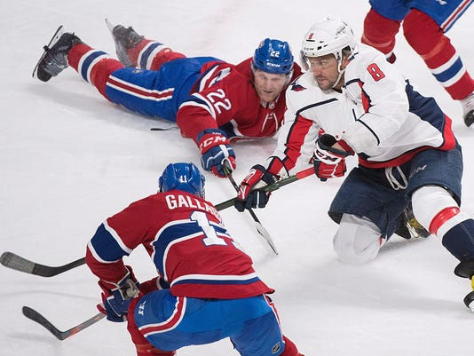 Washington Capitals' Alex Ovechkin (8) moves the puck by Montreal Canadiens' Karl Alzner (22) and Brendan Gallagher (11) during second period NHL hockey action in Montreal, Saturday, March 24, 2018. (Graham Hughes/The Canadian Press via AP)