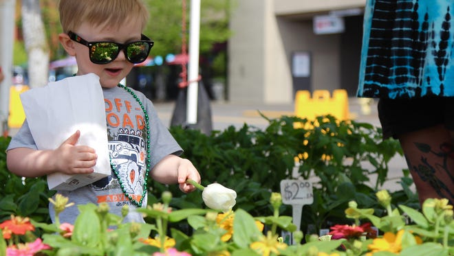 Ezra Green-Kelly, 3, points at flowers he would like to take home on Wednesday, May 3, 2017 on the first day of the Wednesday Market.