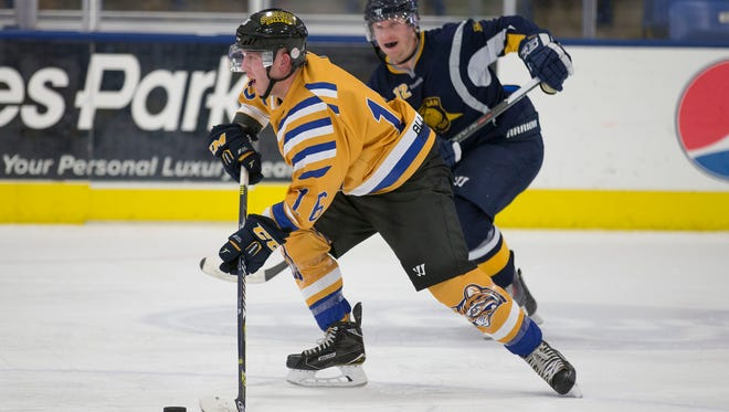 Schoolcraft College's Andrew Lindsay (left) gains a step on older brother Robert Lindsay, of the Michigan State Police hockey team. The teams played a charity game Friday at USA Hockey Arena in Plymouth.