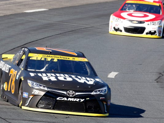 Martin Truex Jr. (78) holds a lead on Kyle Larson (42) during practice for Sunday's NASCAR Sprint Cup Series auto race at New Hampshire Motor Speedway Saturday, Sept. 24, 2016, in Loudon, N.H. (AP Photo/Jim Cole)