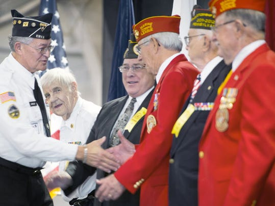 Frank Davila, left, walks down a gauntlet of former Veterans' Meritorious Service Award winners at the York Expo Center Sunday November 11, 2012 in York after receiving the award during the annual Veterans Day Program.  Hometown Heroes allows veterans, such as the men pictured here, to take advantage of a discount program with area businesses. YORK DAILY RECORD/SUNDAY NEWS - PAUL KUEHNEL