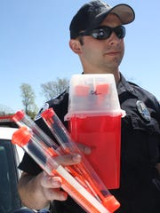 Fort Thomas Police officer Derek Faught holds out a sharps container and three additional syringes that he found while patrolling. Northern Kentucky and Greater Cincinnati have struggled with discarded, contaminated needles since the heroin epidemic began. Northern Kentucky Health Department is urging communities to have syringe exchanges.