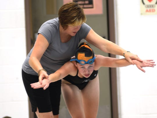 Marine City swimming head coach Sarah Blackstock helps a swimmer with her form during practice on Wednesday Aug. 17, 2016 at Marine City High School.