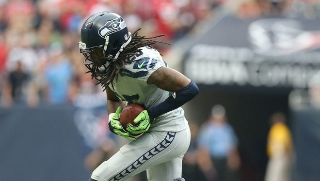 Seattle Seahawks cornerback Richard Sherman (25) intercepts the ball in the fourth quarter against Houston Texans tight end Owen Daniels (81) at Reliant Stadium on Sept. 29, 2013. The Seattle Seahawks beat the Houston Texans 23-20. in overtime.