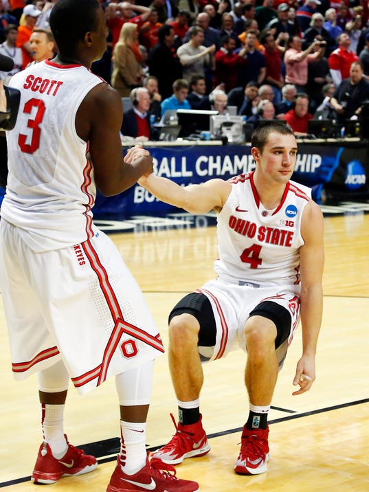 Ohio State's Shannon Scott (3) helps up Aaron Craft (4) after a second-round game in the NCAA college basketball tournament in Buffalo, N.Y., Thursday, March 20, 2014. Dayton won 60-59. (AP Photo/Bill Wippert)