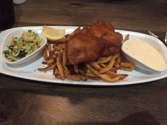 The reel grouper & fries ($24) comes beer-battered with a side of vegetable slaw, malt vinegar tartar sauce and garlic parmesan fries.