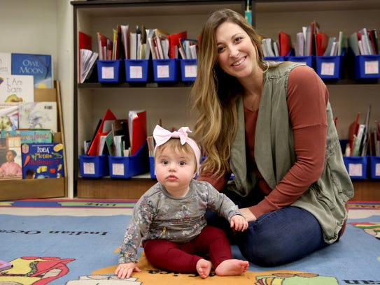Taylor Miller, nee Keeker, sits with her 8-month-old
