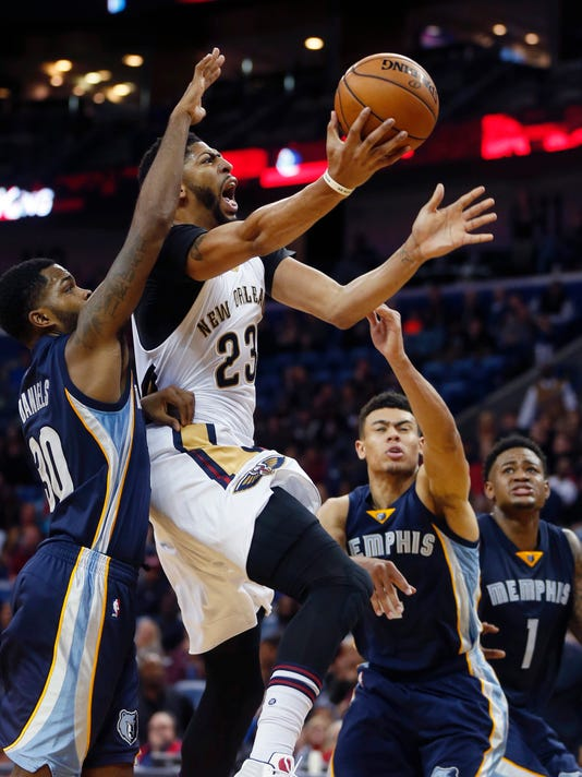 New Orleans Pelicans forward Anthony Davis (23) goes to the basket betweenMemphis Grizzlies guard Troy Daniels (30) and guard Wade Baldwin IV, in the second half of an NBA basketball game in New Orleans, Monday, Dec. 5, 2016. The Grizzlies won in double overtime 110 to 108. (AP Photo/Gerald Herbert)