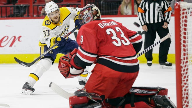 Nashville Predators' Viktor Arvidsson (33), of Sweden, shoots past Carolina Hurricanes goalie Scott Darling (33) to score during the first period of an NHL hockey game in Raleigh, N.C., Sunday, Nov. 26, 2017. (AP Photo/Gerry Broome)