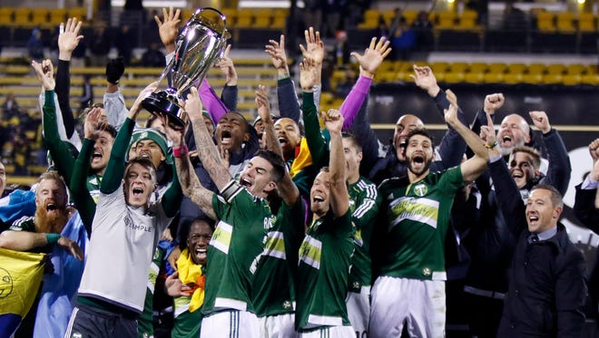Portland Timbers raise the trophy after defeating the Columbus Crew 2-1 in the MLS Cup championship soccer game in Columbus, Ohio. After celebrating its 20th anniversary a year ago with an appreciation for the ups and downs that got MLS to age 20, the league is now moving into its next stage of continuing growth while competing with other leagues around the world.  (AP Photo/Paul Vernon, File)