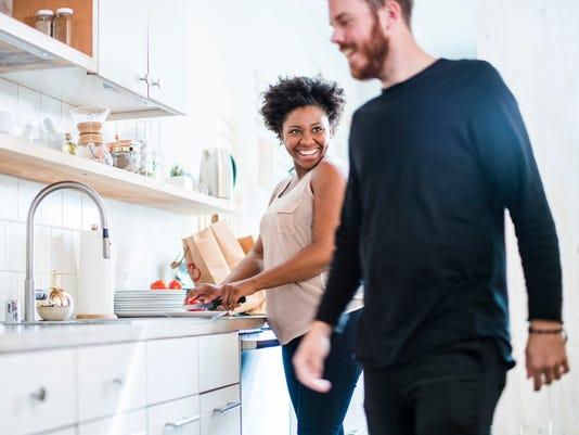 Young pretty black woman make soup in kitchen