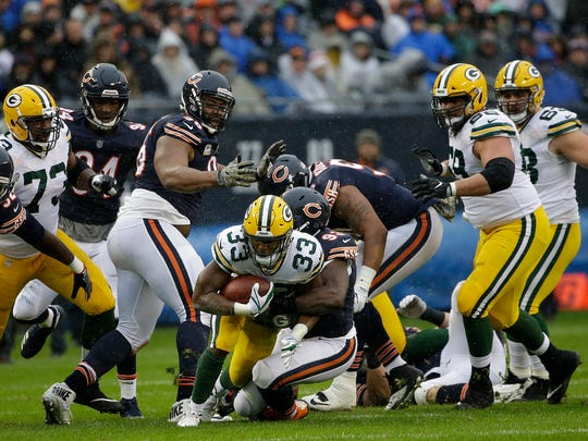 Chicago Bears outside linebacker Sam Acho (93) tackles Green Bay Packers running back Aaron Jones (33) during the first half of an NFL football game Sunday in Chicago.