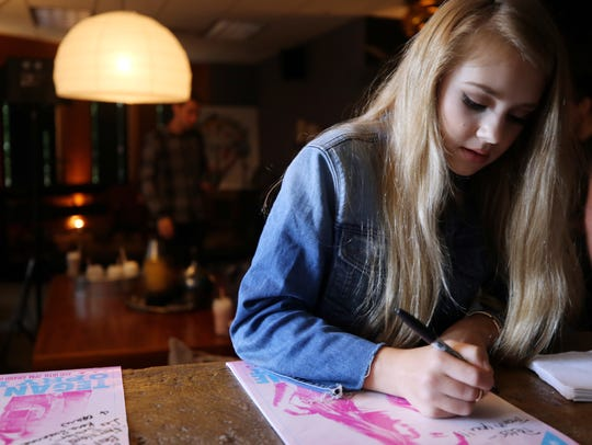 Tegan Marie signs a poster for her Opry debut at Warner