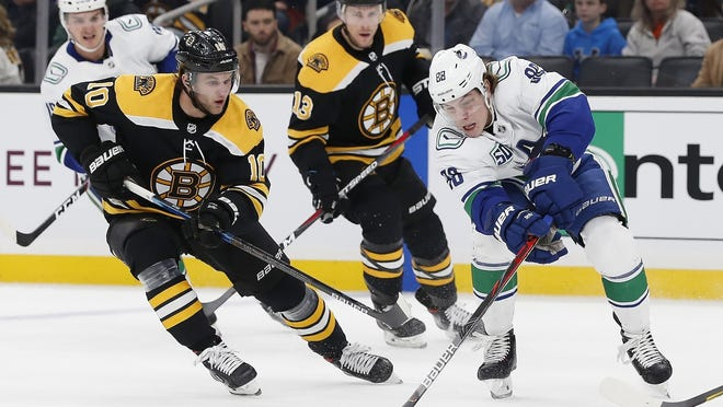 Boston's Anders Bjork (10) and Vancouver's Adam Gaudette (88) battle for the puck during the first period Tuesday night.