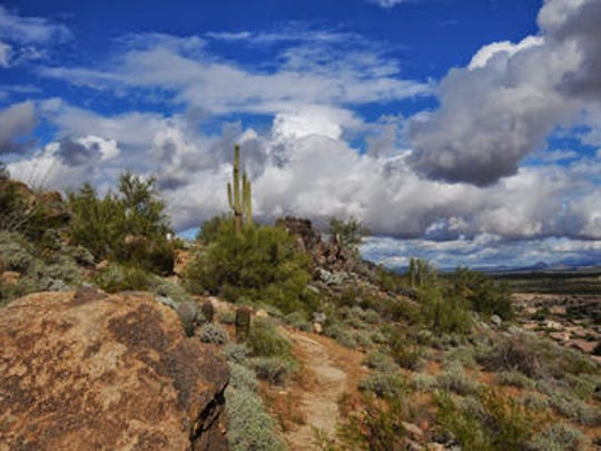 Desert clouds hover above the East Wing Mountain trails