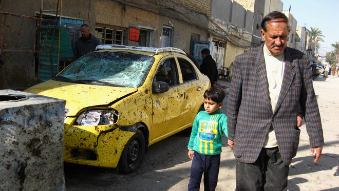People walk past damaged vehicles following a car bomb attack in Baghdad on Sunday.