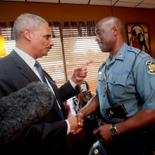 Attorney General Eric Holder talks with Capt. Ron Johnson of the Missouri State Highway Patrol on Aug. 20, 2014, in Florrissant, Mo.