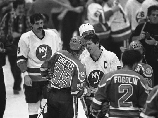 Islanders captain Denis Potvin shakes hands with Oilers captain Wayne Gretzky, after N.Y. won a fourth consecutive Stanley Cup, May 17, 1983.
