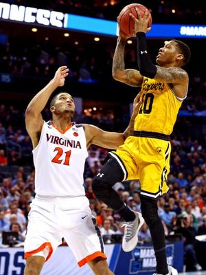 Mar 16, 2018; Charlotte, NC, USA; UMBC Retrievers guard Jairus Lyles (10) shoots the ball against Virginia Cavaliers forward Isaiah Wilkins (21) during the second half in the first round of the 2018 NCAA Tournament at Spectrum Center. Mandatory Credit: Jeremy Brevard-USA TODAY Sports