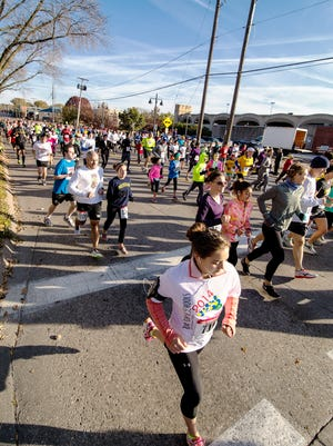 """Runners participating in the 5k, 10k, and half-marathon make their way down the courses on Gilbert Street as part of the """"Run for the Schools"""" in downtown Iowa City on Sunday, Oct. 18, 2014."""