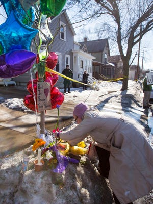 Mary Jo Walters places a flower on a makeshift memorial for Tony Robinson in Madison, Wis., on Sunday, March 8, 2015.