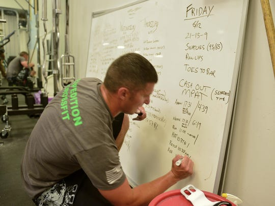 Matt Fleming of the Great Falls Police Department records his workout time on a whiteboard in the police department weight room. Documenting workout results helps with goal setting and motivation for future workouts.