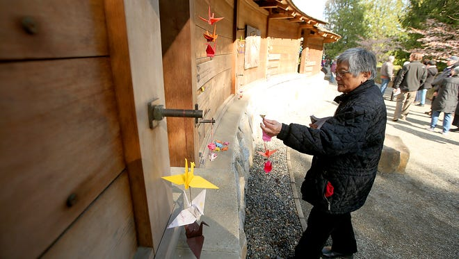 Yasuko Hayashida Mito, of Kent, hangs a strand of origami cranes Thursday next to her name, which adorns the Bainbridge Island Japanese American Exclusion Memorial. Mito was 5 when she and her family were sent to internment camps.