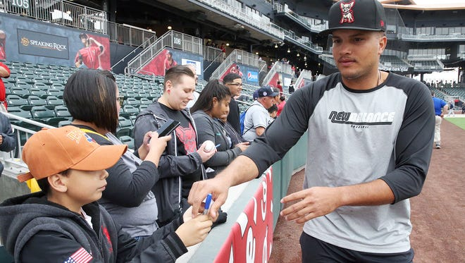 El Paso Chihuahuas third baseman Diego Goris signs autographs for fans, including Aaron Eduardo Martinez, 10, of El Paso, before the start of the Chihuahuas exhibition game with their parent team, the San Diego Padres, on Monday night