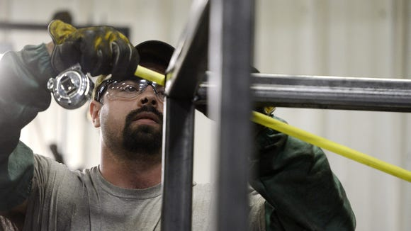 A laborer measures a metal frame that will house a