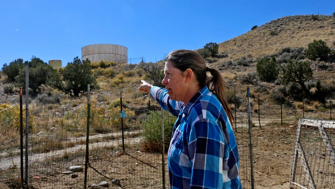 Harvest Gold subdivision resident Peggy Hogan talks about the water tanks located above her home Oct. 11 east of Bloomfield. Customers of the troubled water system have been without clean water for much of the year.