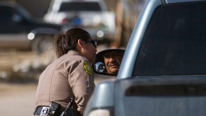 Navajo Nation Police Officer Felicia Freeman talks with a motorist during a traffic stop Thursday in Shiprock.