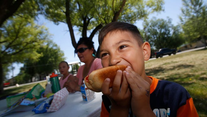 Abel Archuleta enjoys lunch with his grandmother Joann Atencio and sister Nevaeh Archuleta during a summer food kickoff event  in Bloomfield on May 31.
