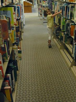 Katie Butler, a 6-year-old in this June 2008 file photo, reaches for a book at the Vogelson Library in Voorhees.