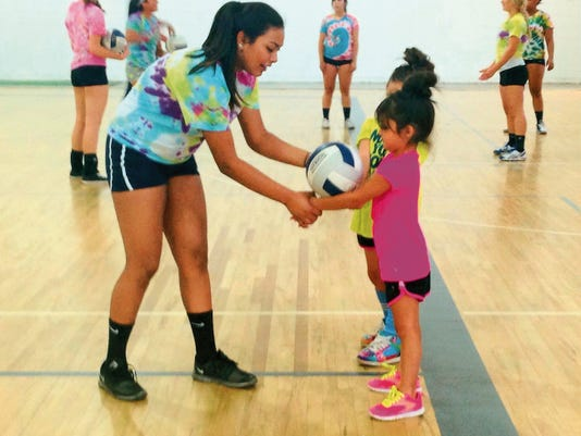 Courtesy Photo   Silver High volleyball player Aubrey Salas, left, helps camper Everleigh Aguirre and Lily Meley with their passing platform during action at Silver's volleyball youth camp.