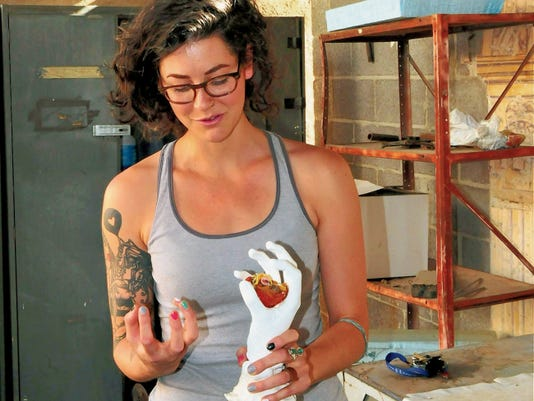 Local artist Cassie Dixon shows off one of her hand molds, part of a series of hands holding objects found in nature.