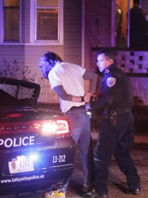 Lafayette police officers detain Jordan Thomas as they investigate a reported shooting at a home on Schuyler Street on Dec. 20, 2015.