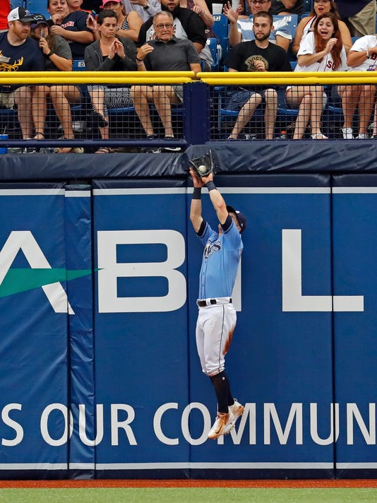 Tampa Bay Rays left fielder Corey Dickerson makes a leaping catch on a fly ball by Boston Red Sox's Jackie Bradley Jr. during the sixth inning of a baseball game Sunday, July 9, 2017, in St. Petersburg, Fla. (AP Photo/Mike Carlson)