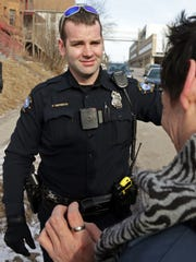 In this Feb. 2, 2015 photo, a red light on the body camera worn on Duluth, Minn. police officer Dan Merseth's uniform indicates it is active prior to taking a man, right, to a detox center in Duluth.