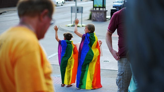 Parker Gaddis, 6, of Sioux Falls, and Alaina Townsend, 9, of Canton, S.D., wave to passersby before a vigil in downtown Sioux Falls Monday, June 13, 2016, in response to the mass shooting at the Pulse nightclub in Orlando, Fla. Dozens of vigil participants marched from 11th Street and Phillips Avenue to Club David at the corner of 10th Street and Dakota Avenue in Sioux Falls. The vigil was put on by the South Dakota Peace and Justice Center and the Center for Equality.