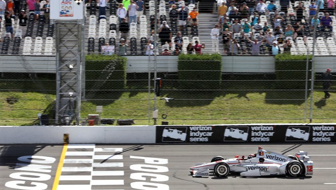 Will Power, of Australia, (12) pumps his fist as he takes the checkered flag to win the Pocono IndyCar 500 auto race Monday, Aug. 22, 2016, in Long Pond, Pa. Mikhail Aleshin, of Russia, (7) was second. (AP Photo/Mel Evans)