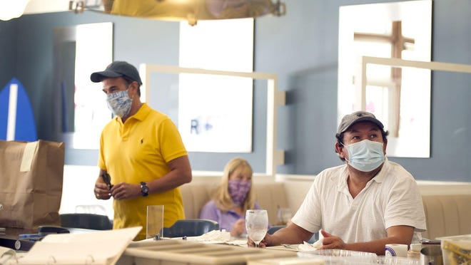 The lunch crowd at SurfSide Diner complied with the Palm Beach County mask mandate on Friday.
