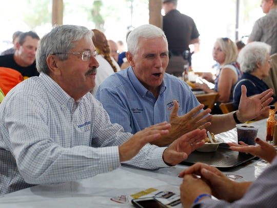 Former Iowa Gov. Terry Branstad and then-Indiana Gov. Mike Pence chat as Pence sits down to a hot beef sundae Saturday, Aug. 20, 2016, at the Cattlemen's Beef Quarters at the Iowa State Fair in Des Moines.