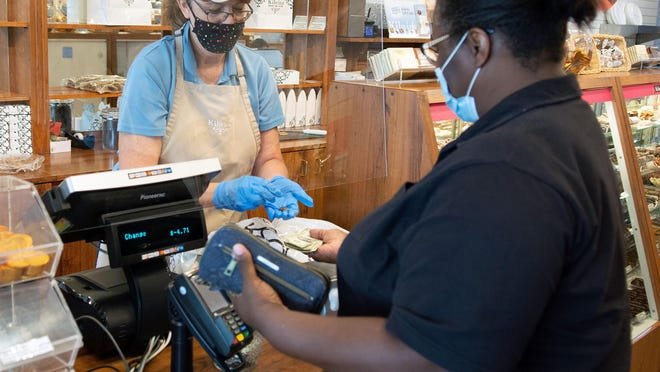 Kilwin's Chocolates Manager Jennifer Haack is able to use coins when giving change to Charlisa Garrett during a recent visit to the Hendersonville store by the Trenton, South Carolina resident. A nationwide coin shortage has caused headaches for some area retailers.