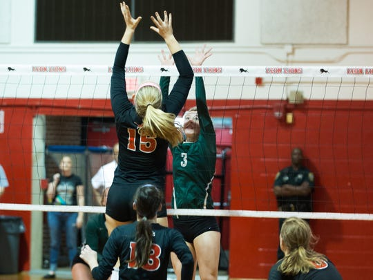 Leon junior middle hitter Caroline Kirk tries to beat Lincoln's Kaylyn Buchanan to a tip at the net. Kirk's presence in the middle was a giant factor in the Lions' 3-1 win over the Trojans in a regional semifinal.