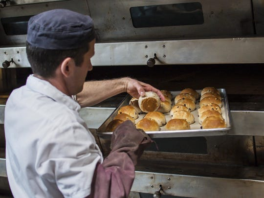 Pastry chef Jeremy Gullen checks on hot cross buns cooking at Red Hen Bakery in Middlesex.