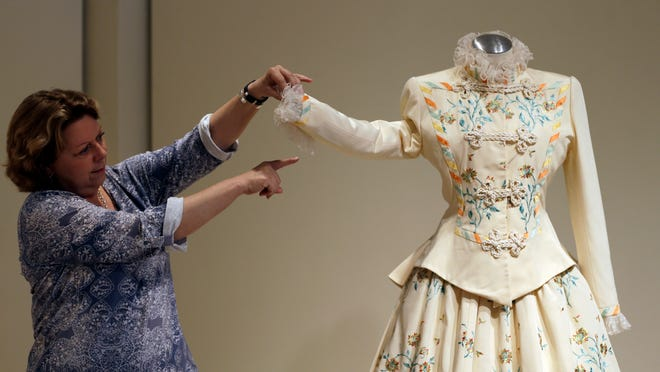 """In this photo taken on Tuesday, July 1, 2014, curator Myra Walker, left, discuses a 1993 wedding dress designed by Victor Costa that is displayed at the """"American Brides: Inspiration and Ingenuity,"""" exhibition in Denton, Texas. Wedding dresses from the 19th century to now are featured in a new exhibit showcasing the evolving styles of American brides with more than 40 wedding gowns worn over a span from 1844 to last year."""