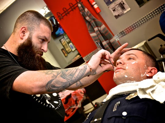 Casey Newman of Styles Barber Shop in Wilmington shaves Wilmington police Cpl. Josh Wilkers during a November fundraising event. Following the event, Wilkers donated his pay for the day.