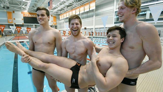 Teammates Peter John Stevens, Ryan Coetzee, and Kyle DeCoursey hold Braga Verhage while posing for a photo at the Allan Jones Aquatic Center Thursday, Mar. 15, 2018.